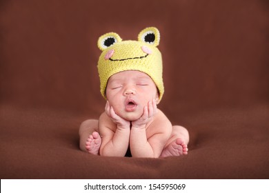 Newborn baby  sleeping, resting on her own hands and elbows, on brown background. Frog hat and frog pose.
