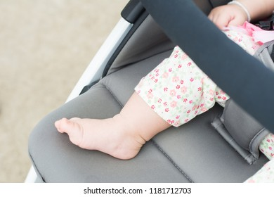 Newborn baby sleeping in stroller outdoors.Small baby barefoot with copy space.