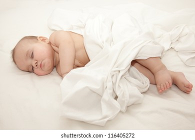 Newborn baby sleeping together with his mother in the bed on white sheets. Mothers hand holding baby. Selective focus on babys head