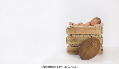 Newborn baby sleeping in a vintage wooden crate on a white backdrop with a rugby ball in front of the crate.