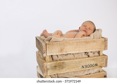 Newborn baby sleeping in a vintage wooden crate on a white backdrop