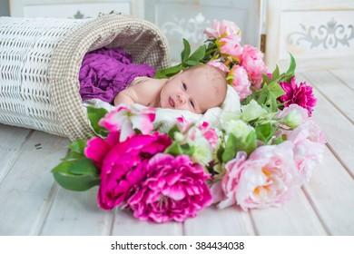 newborn baby sleeping in white basket full of spring  flowers