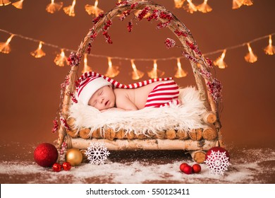 Newborn baby sleeping in a wooden crib. The striped suit elf on a brown background.  Decorated New Year toys.