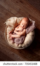 A newborn baby sleeps in a basket on a wooden floor. Beige background. Copy Space. A tender smile of the baby.
