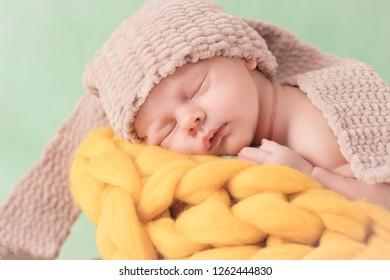 Newborn baby sleeps on a wicker basket with a knitted velvet of yarn. Newborn  baby 1763ac93400b
