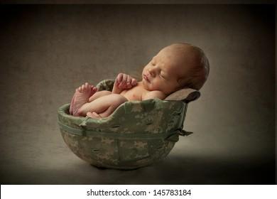 A newborn baby sleeps tucked inside his father's army helmet