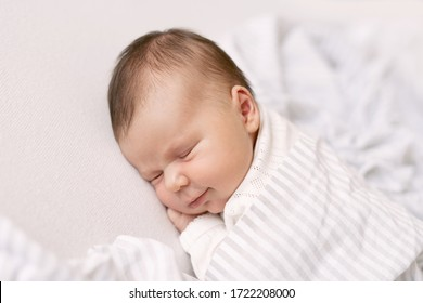 newborn baby sleeps under the covers and smiles