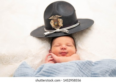 Newborn Baby smiling wearing a law enforcement hat