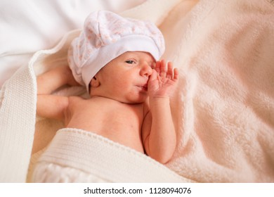 newborn baby strokes his face. Baby is waiting for breastfeeding.