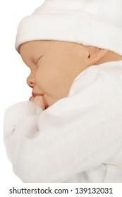 Newborn baby sucking on her thumb on white