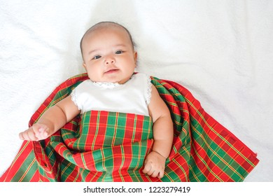 Newborn baby wear white dress and Thai traditional fabric called pa kao ma at bottom, white towel background with shadow