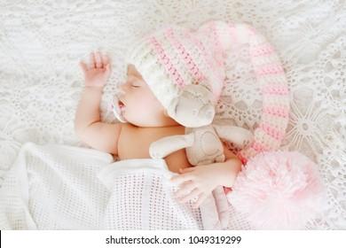 newborn baby wearing huge hat is sleeping