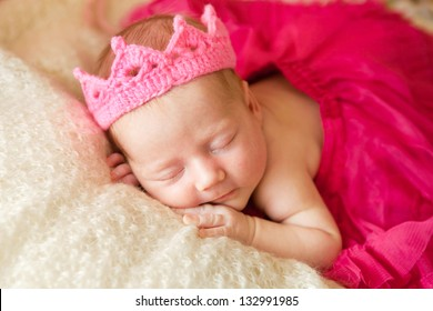 A newborn baby is wearing in a princess costume and sleeping on a soft white background. Childhood or parenting concept.