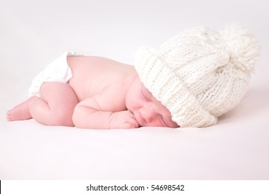 A newborn baby is wearing a white hat and laying down sleeping on a soft  white 6079f7915482