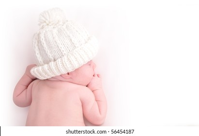 A newborn baby is wearing a white hat and laying down sleeping on a white  isolated 8bb95fe6ce2d