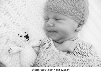 A newborn baby wrapped in a knitted blanket and blue knitted cap. A newborn infant with a toy white bear.