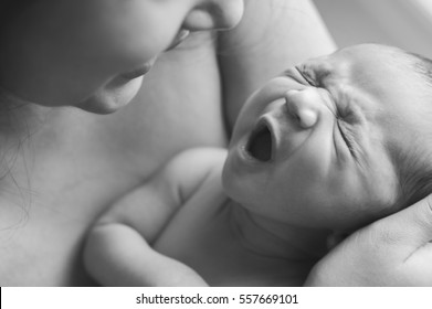 A newborn baby yawning in her mother's arms