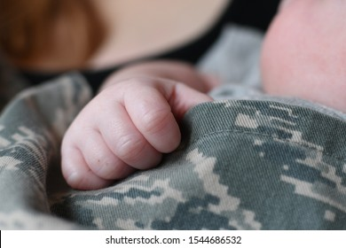 Newborn baby's hand gripping military father's fatigues
