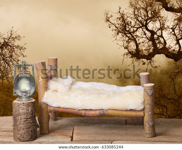 A newborn bed studio digital prop made from Japanese Maple tree branches with a brown nature spooky background and an oak tree in the background with a railroad lantern on a tree stump.