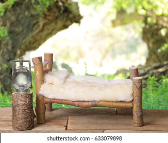 A newborn bed studio photography prop with a railroad lantern and a wooded forest background.  The bed is handmade from a Japanese Maple tree.