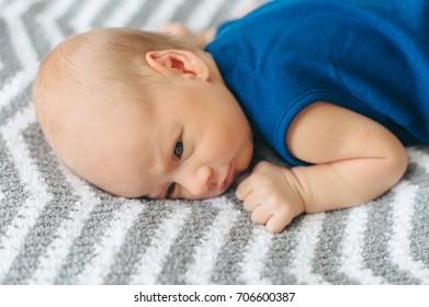 A newborn boy is asleep in bed