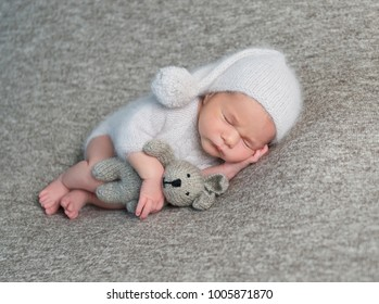Newborn boy sleeping in funny bonnet
