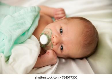 Newborn child lying on bed
