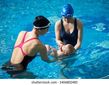 Newborn child lying in swimming pool on his back. Two women in swimwear, cap, goggles, mother and professional instructor holding him and teaching swimming and floating. Blue water on background