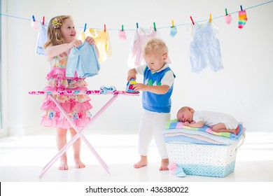 Newborn child on pile of clean dry towels. Brother and sister playing with little sibling. Siblings bonding. Children ironing clothes. Twin kids play with baby boy. New born kid after bath in a towel