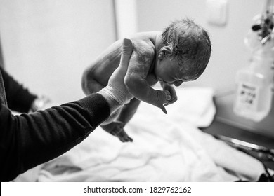 Newborn child seconds and minutes after birth. Doctor hands with new born baby. Medical check up of health and reflexes of child. New life, beginning, healthcare