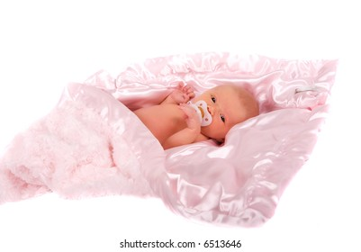 Newborn child with a soother wrapped in a pink blanket