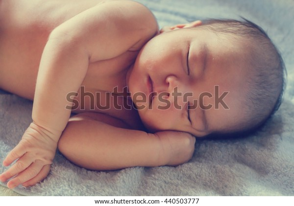 newborn cute Asian baby boy sleeping with blue blanket in vintage tone style : people concept