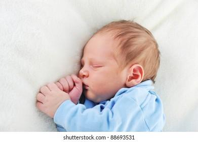 Newborn cute baby sleeping on white blanket