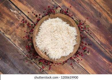 Newborn digital background with white fur in a wooden bowl surrounded by red berries on a wood background