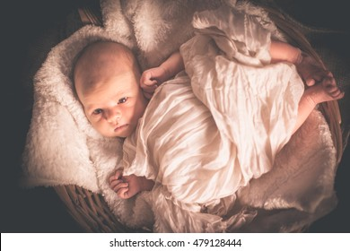 Newborn European baby Boy Closeup Sleeping in Basket with Brown and white Blanket, Shallow Depth of Field