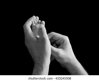 Newborn feet inside a his dad or mom hand isolated on black background