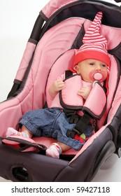 Newborn girl in child safety seat.
