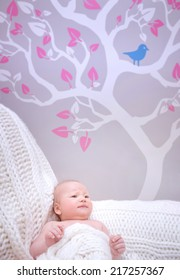 Newborn girl in cute baby room, gentle stylish interior of bedroom, beautiful picture on wallpaper, happy childhood concept