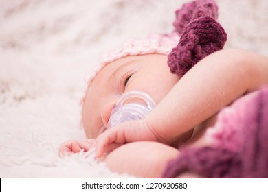 Newborn girl with pacifier
