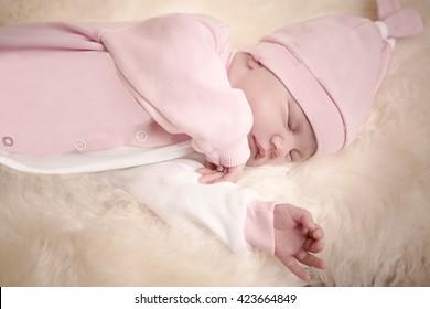 newborn girl in a pink dress sleeping on sheep skin on a light background