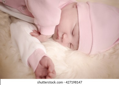 newborn girl in a pink dress sleeping on sheep skin
