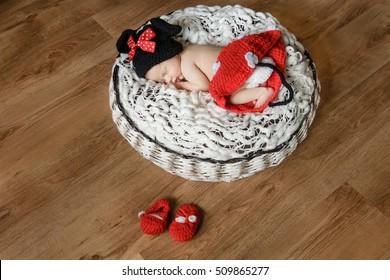 Newborn girl sleeping in basket in Minnie Mouse dress