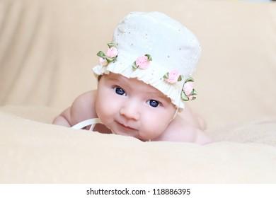newborn girl in white cap with flowers