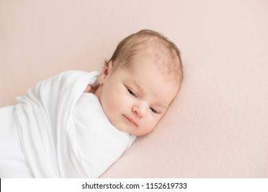 Newborn girl in white wrap on a pink background. Photoshoot for the newborn. 7 days from birth. A portrait of a beautiful, seven day old, newborn baby girl