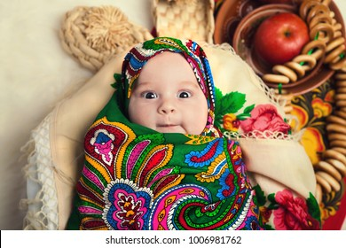 newborn girl wrapped in Russian national ethnic scarf in the form of russian nesting dolls or cocoons, next to bast shoes, clay dishes with apples and bagels, close-up