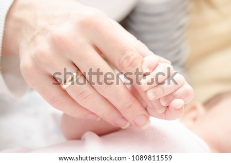 The newborn holds the mother's hand