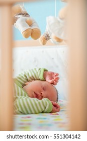 A newborn infant sleeping in his bed.