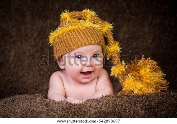 Newborn in knitted winter hat on a beige background.