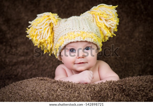 Newborn in knitted winter hat on a beige background.