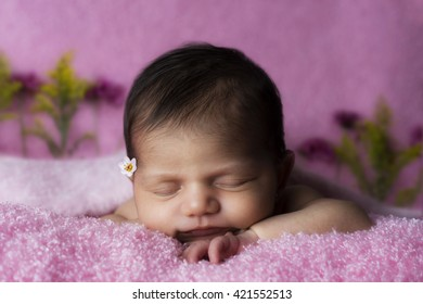 Newborn laying down on a pink soft blanket